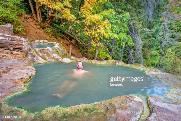 man relaxes in umpqua hot springs in oregon usa - hot spring stock pictures, royalty-free photos & images