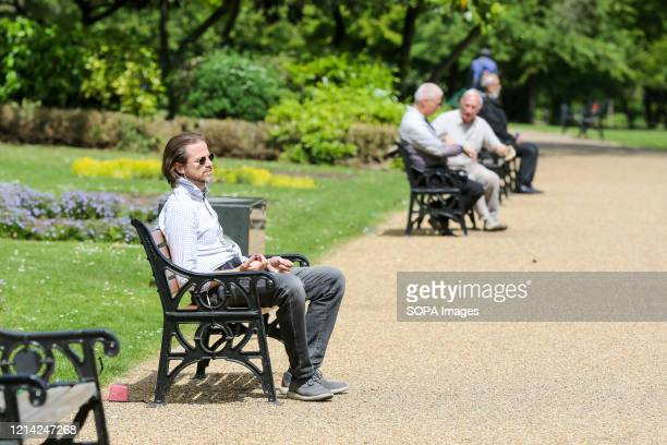 Man relaxes on a park bench at Finsbury Park on a warm and sunny day during the covid 19 crisis. The UK government relaxed the guidelines on...