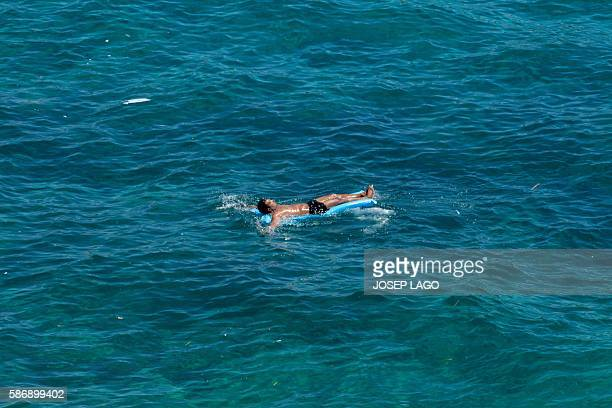A man relaxes on an inflatable lilo off the the Catalonian coastal city of Lloret de Mar along the Mediterranean Sea on August 7 2016 / AFP / JOSEP...