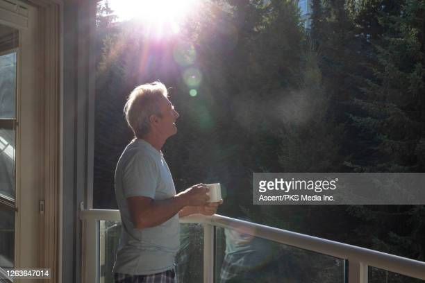 man relaxes on balcony in the forest at sunrise - early retirement stock pictures, royalty-free photos & images