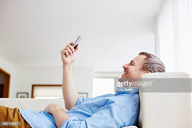 man relaxes on couch at home smiling at his phone - stralende lach stockfoto's en -beelden