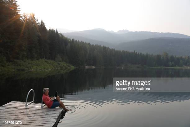 man relaxes on dock above lake, uses laptop computer - media_(communication) stock pictures, royalty-free photos & images