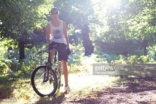 man relaxes on his mountain bike in a sunlit fores - forens stock pictures, royalty-free photos & images