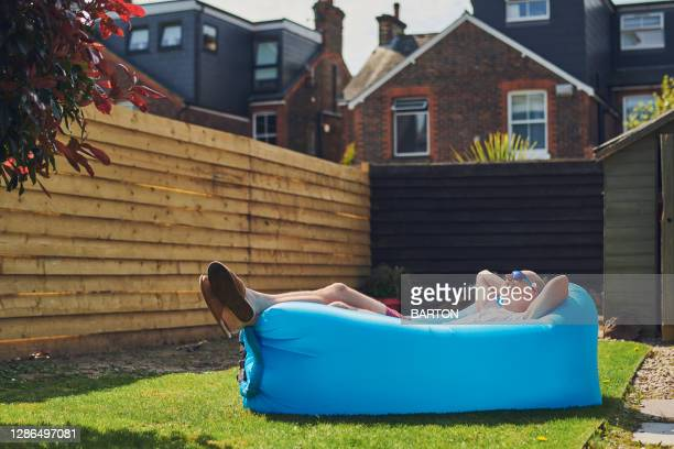 man relaxes on inflatable lounger in garden at home - relaxation stock pictures, royalty-free photos & images