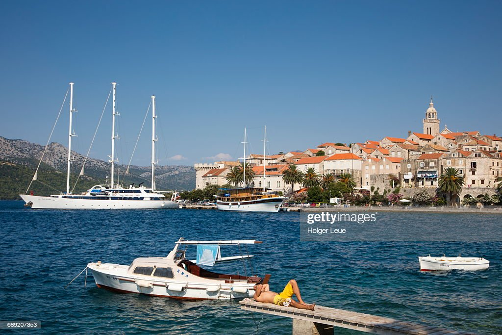 Man relaxes on jetty with Korcula Old Town behind : Stock Photo