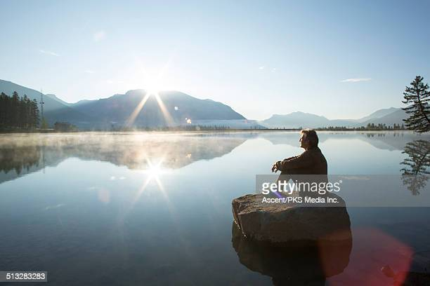 Man relaxes on rock island, mountain lake