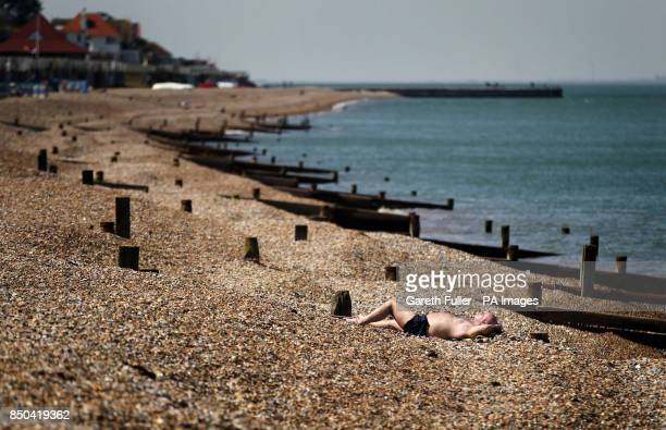A man relaxes on the beach in Herne Bay Kent as the warm weather continues