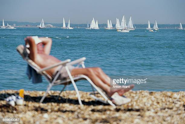 Man relaxes on the beach to sunbathe as sailing yachts race against each other during Cowes Week on 5 August 1995 off Cowes on the Isle of Wight,...