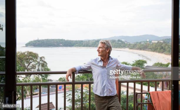 Man relaxes on veranda, above beach, sea