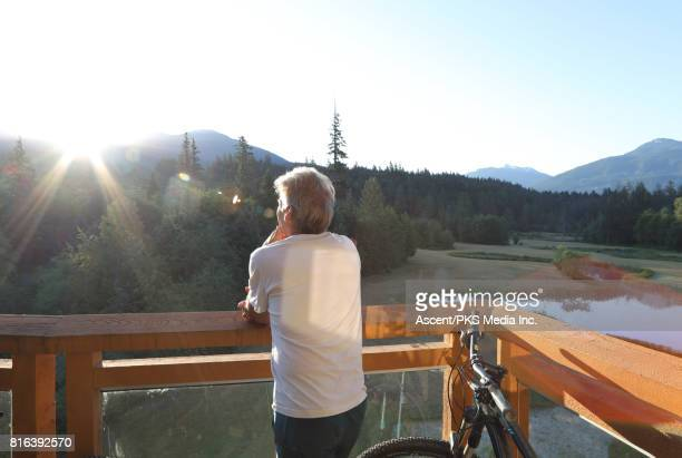 Man relaxes on veranda, looks out to mountains