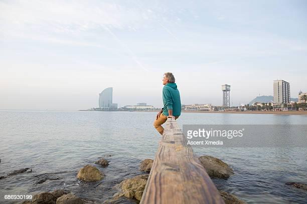 man relaxes on waterfront rail, looks to sea - entfernt stock-fotos und bilder