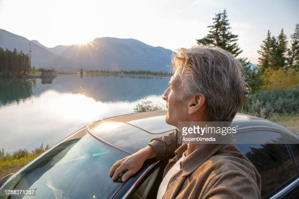 man relaxes outside car beside lake in the morning - one mature man only stock pictures, royalty-free photos & images