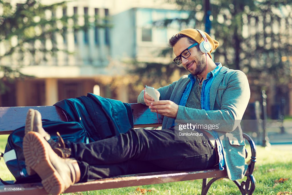 man relaxing after work in a park using his smartphone : Stock Photo