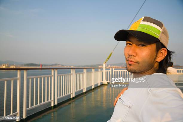 Man relaxing and looking at camera on ferry deck