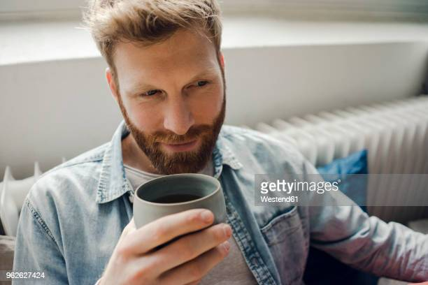 man relaxing at home, drinking coffee - mann kaffee stock-fotos und bilder