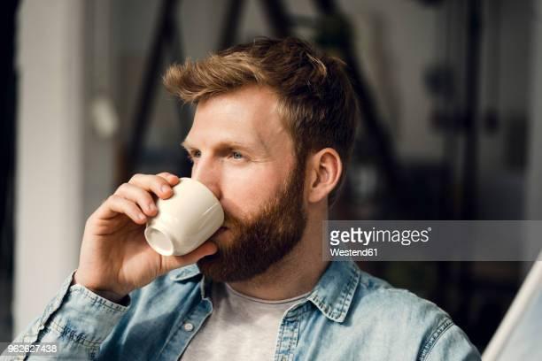 man relaxing at home, drinking coffee - trinken stock-fotos und bilder