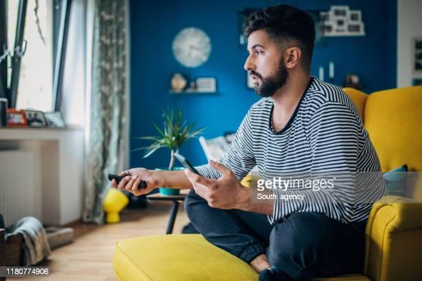 自宅でくつろぐ男 - テレビを見る ストックフォトと画像