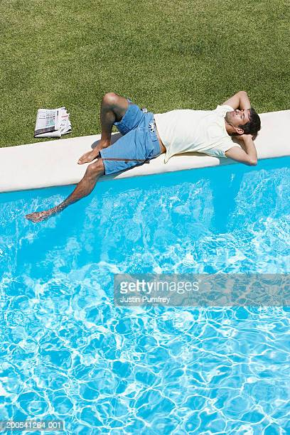 Man relaxing at poolside, elevated view