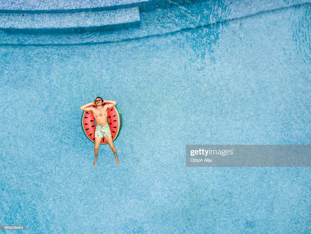 Man relaxing at swimming pool : Stock Photo
