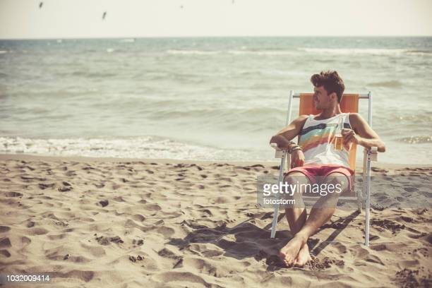 man relaxing at the beach - outdoor chair stock pictures, royalty-free photos & images