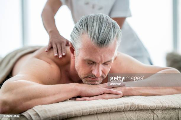 hombre relajante en el spa para un masaje - masaje hombre fotografías e imágenes de stock