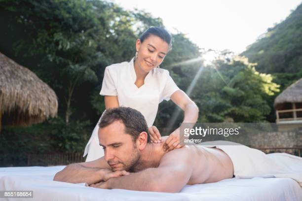hombre relajante en el spa con un masaje de espalda - masaje hombre fotografías e imágenes de stock