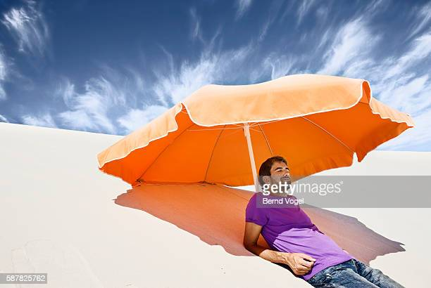 Man Relaxing Beneath Umbrella