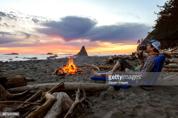 man relaxing by campfire at seashore during sunset - one man only stock pictures, royalty-free photos & images