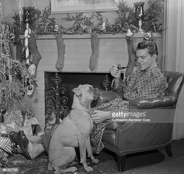 Man relaxing by fireplace with dog at Christmas