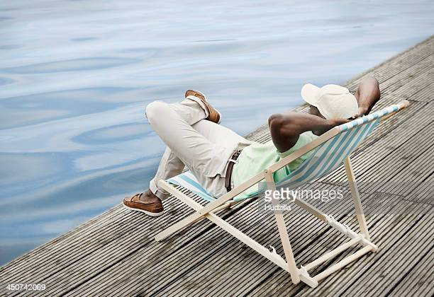 Man relaxing by lake on deck chair