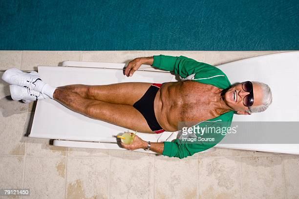 hombre relajante junto a la piscina - white pants fotografías e imágenes de stock