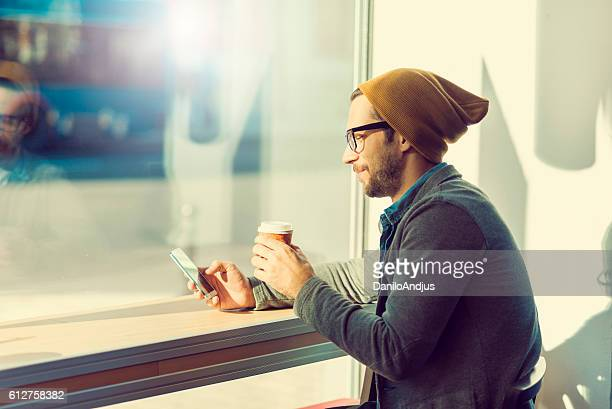 man relaxing drinking coffee and playing with his smartphone