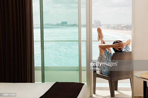 Man Relaxing, Enjoying Hotel Balcony Sea View on Beach Vacation