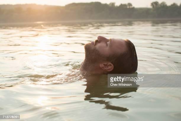 man relaxing, floating in river - flotter sur l'eau photos et images de collection