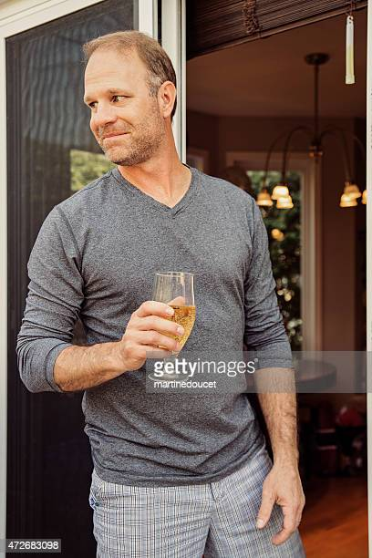 Man relaxing getting out of his house with a beer.