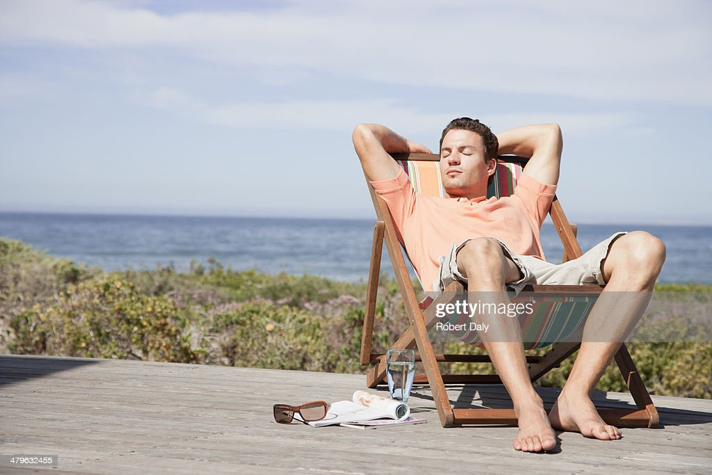Man relaxing in a lounge chair : Stock Photo
