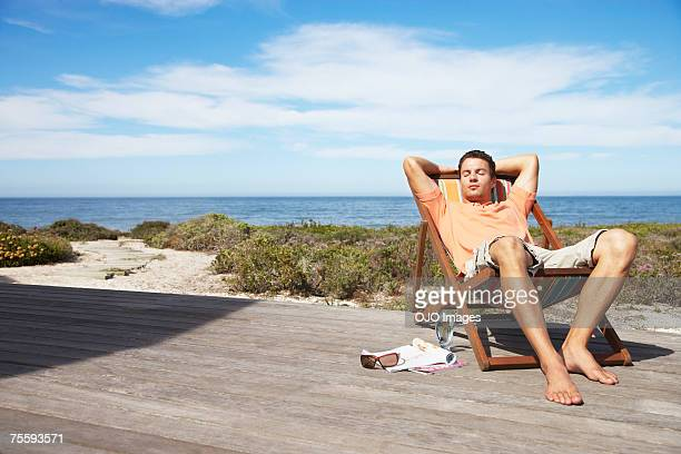 man relaxing in a lounge chair - outdoor chair stock pictures, royalty-free photos & images