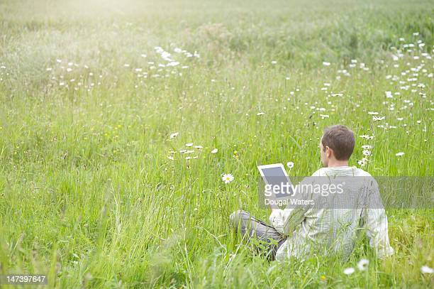 man relaxing in a summer meadow with a tablet - newtechnology stock pictures, royalty-free photos & images