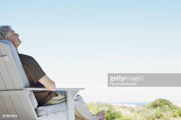 Man relaxing in Adirondack chair
