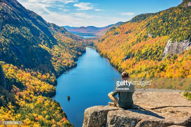 man relaxing in adirondack mountains new york state usa during fall colors - new york state stock pictures, royalty-free photos & images