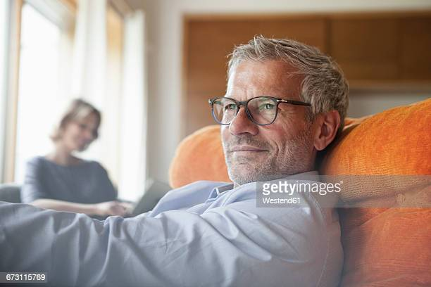 man relaxing in armchair with wife in background - ehefrau stock-fotos und bilder