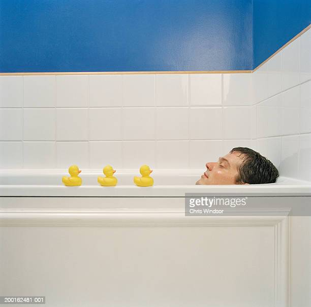 Man relaxing in bath with row of rubber ducks along edge, profile