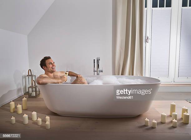 Man relaxing in bathtub with glass of champagne