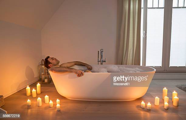 Man relaxing in bathtub with lighted candles arround