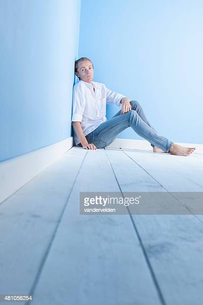 man relaxing in blue jeans and white shirt - floorboard stock photos and pictures