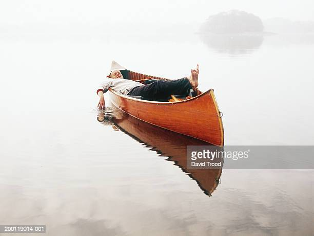 Man relaxing in canoe on still lake, trailing one hand in water