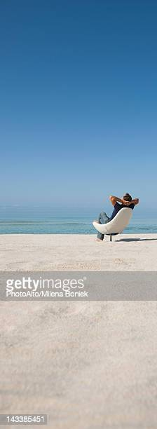 Man relaxing in chair on beach, rear view