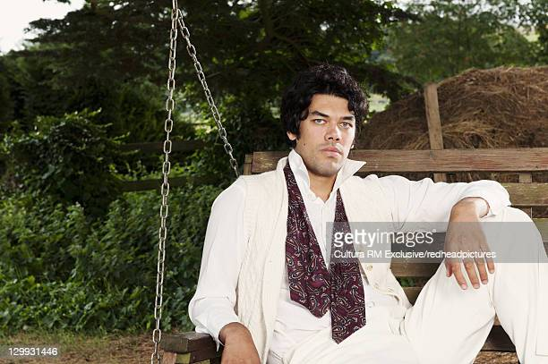 man relaxing in chair swing - newpremiumuk stock pictures, royalty-free photos & images