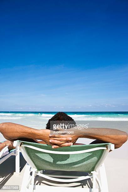 man relaxing in chaise lounge chair on beach - playa del carmen stock pictures, royalty-free photos & images