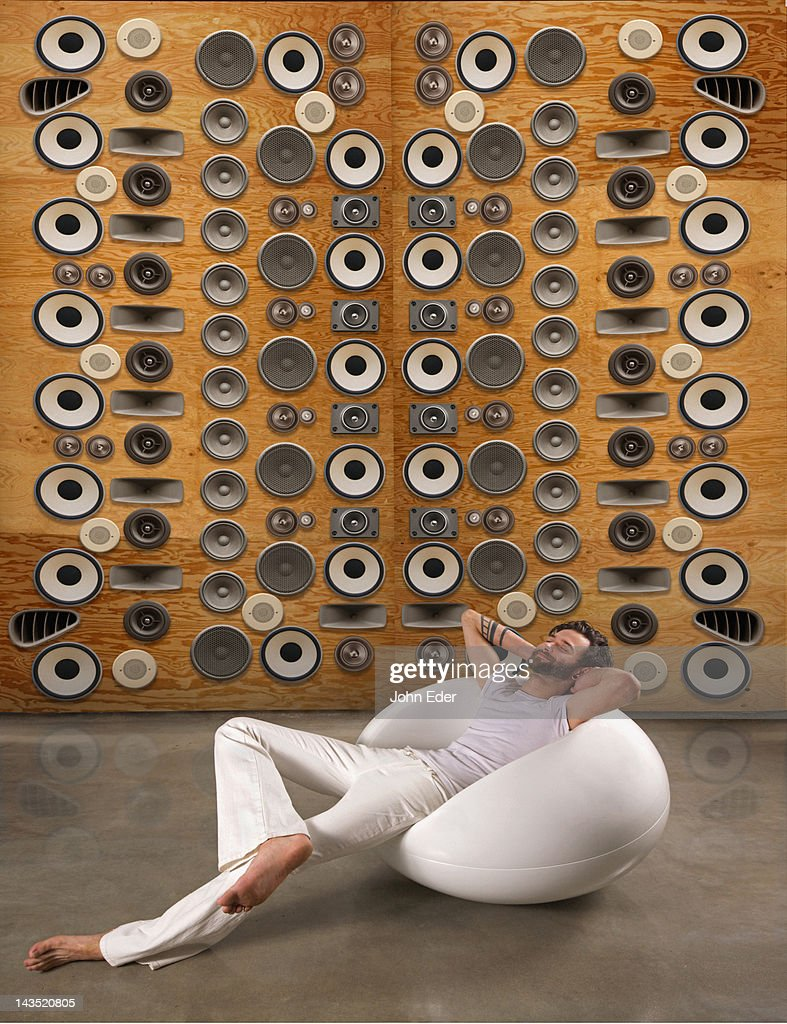 Man Relaxing In Front of Wall of Speakers : Stock Photo